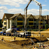 excavator and workers lay foundation infrastructure for new housing development