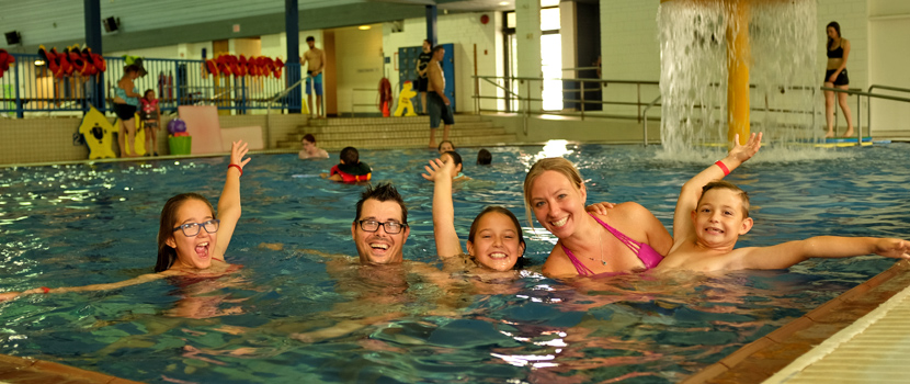 Family of 5 swimming int he four seasons leisure pool